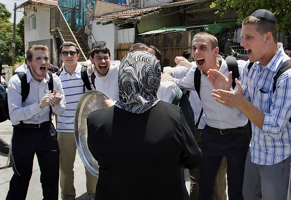 Israelis taunt an Arab woman whose home has been occupied by settlers.